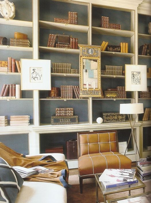 I love the effect of hanging artwork or mirrors on the bones of the bookshelves...